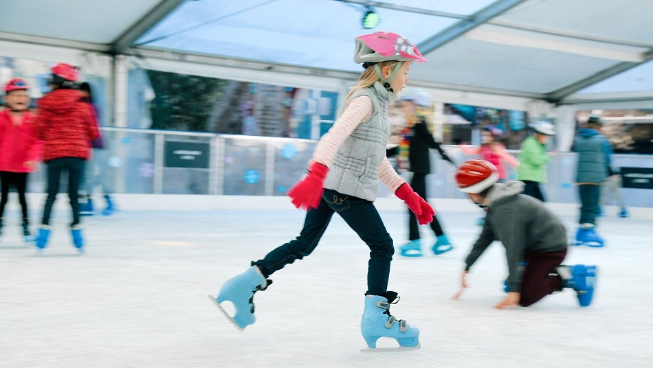 Young girl ice skating on pop up ice rink