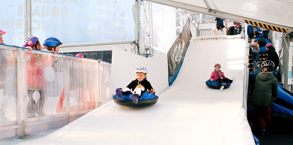 Children tobogganing down a fake ice hill