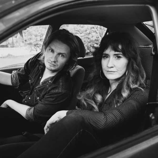 Black and White photo of two people in a car with window down