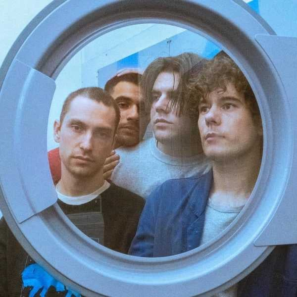 photo of four men looking through the door of a washing machine