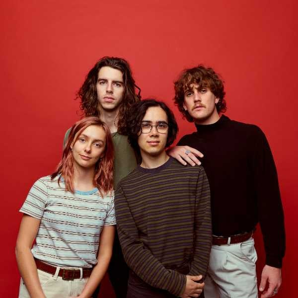 Photo of three guys and one girl standing in front of a bright red backdrop