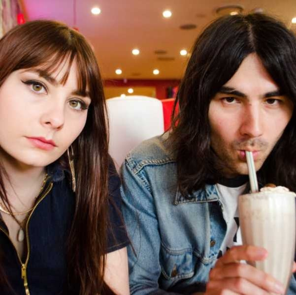 Photo of two people in a diner drinking a milkshake