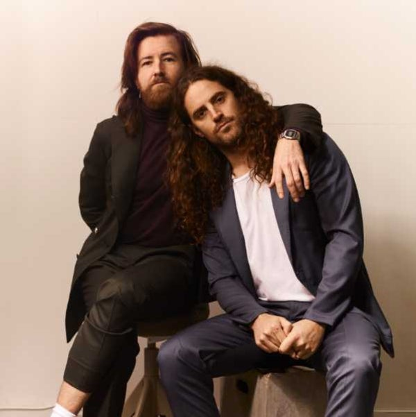 Photo of two male musicians sitting on stools wearing suits
