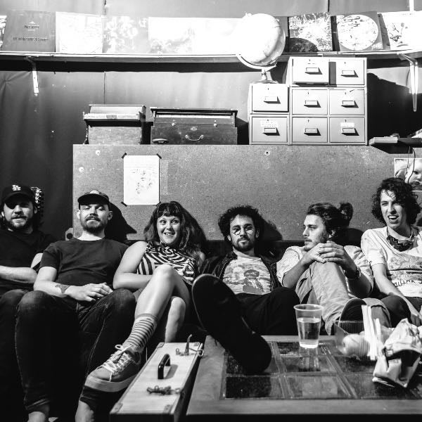 Black and white photo of six people sitting on a couch smiling