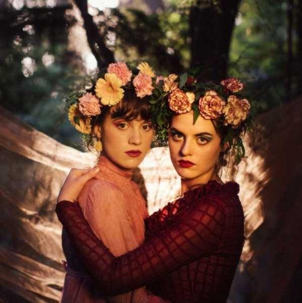 Photo of two girls hugging wearing matching flower crowns