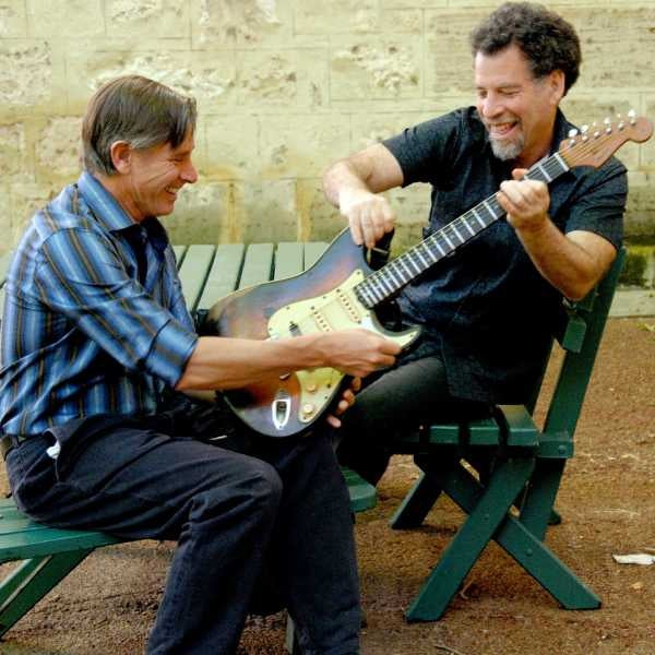 Photo of two men smiling and holding an electric guitar between them